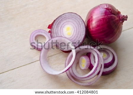 Sliced fresh purple onion isolated on wooden background. Full and chopped onion. Closeup. Carved crimean onion. - stock photo