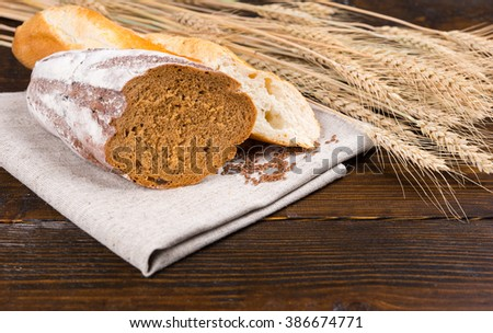 Sliced fresh rye bread and crusty baguette showing the texture of the loaf on a wooden table with fresh ripe ears of wheat - stock photo