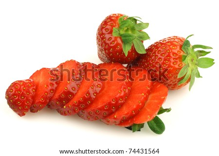 sliced fresh strawberry and two whole ones on a white background