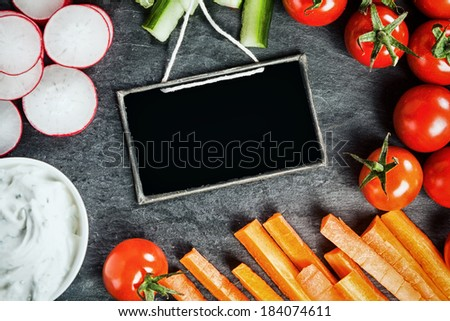 Sliced fresh vegetable frame around a small blank vintage school slate including radish, carrot batons, tomato and cucumber served as crudites with savory dip - stock photo