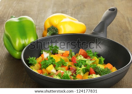 Sliced fresh vegetables in pan with spices and ingredients on wooden table - stock photo