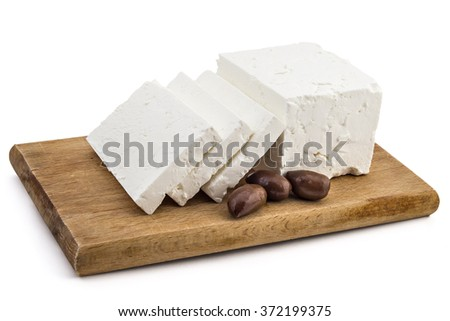 Sliced fresh white cheese from cow's milk with kalamata black olives on wooden board and white background - stock photo