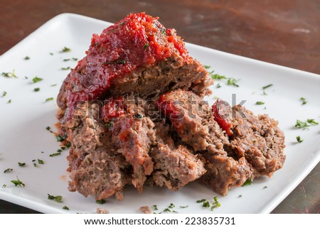 Sliced freshly cooked traditional meatloaf with ketchup tomato sauce isolated on white plate - stock photo