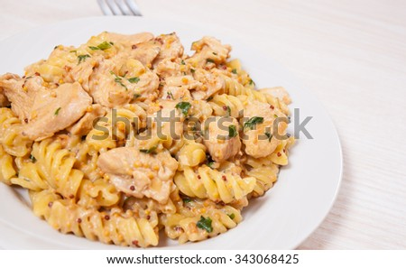 Sliced fried chicken fillet in a creamy and mustard sauce. with fusilli pasta - stock photo