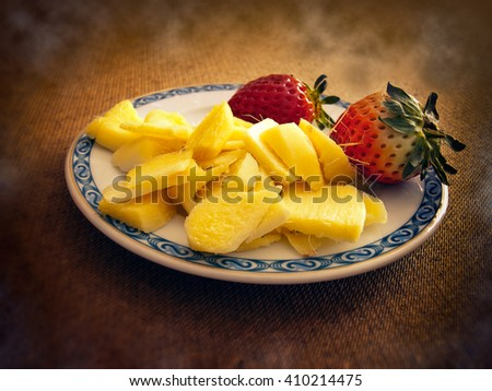 Sliced Ginger and two strawberries on a little plate.