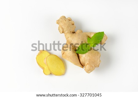 sliced ginger with mint on off-white background with shadows - stock photo