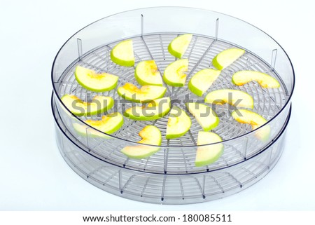 sliced green apple in Food dryer on white background - stock photo