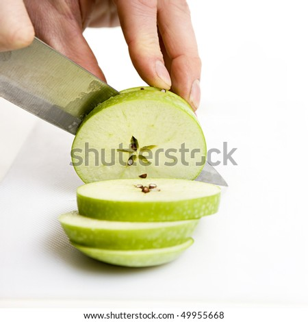 sliced green apple in multiple pieces with knife - stock photo