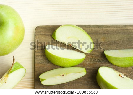 sliced green apple on wooden cutting board - stock photo