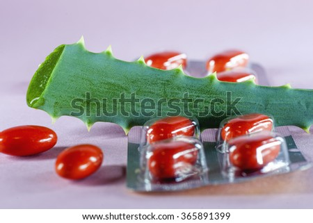 Sliced green leaves of aloe with homeopathic red capsules on a light pink background - stock photo