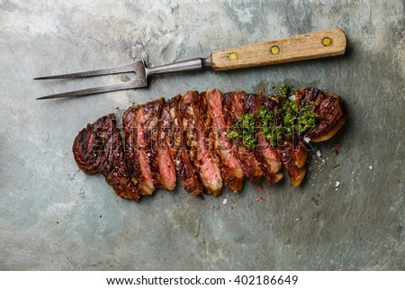 Sliced grilled beef barbecue Striploin steak with chimichurri sauce and meat fork on gray stone slate background - stock photo