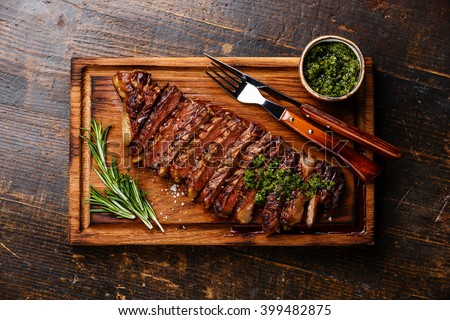Sliced grilled beef barbecue Striploin steak with chimichurri sauce on cutting board on dark wooden background - stock photo