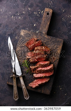 Sliced grilled Beef steak with knife and fork for meat on wooden cutting board - stock photo