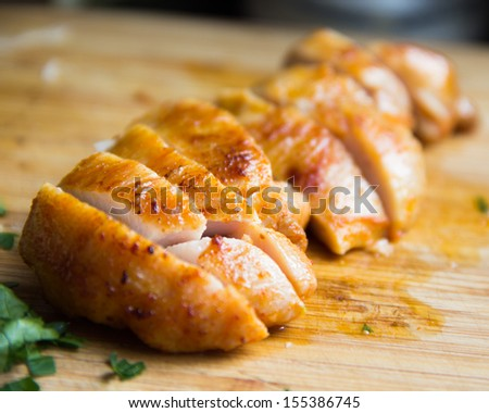 Sliced grilled juicy chicken fillet on wooden board macro, clouse up - stock photo