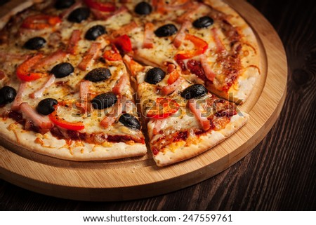 Sliced ham pizza with capsicum and olives on wooden board on table - stock photo
