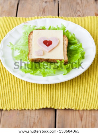 Sliced ham sandwich with lettuce, tomato and cheese