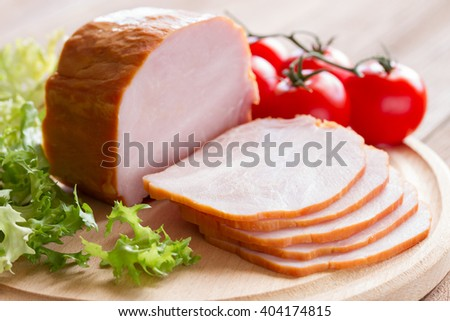 Sliced ham with tomatoes and lettuce on a wooden background . close-up - stock photo