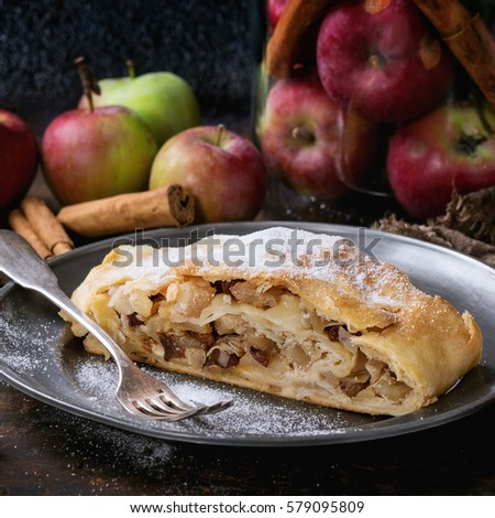 Sliced homemade apple strudel served with fresh apples in glass jar, cinnamon sticks and sugar powder on vintage metal plate with fork over old wooden background. Dark rustic style. Square image