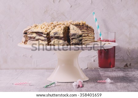 Sliced Homemade Birthday Honey Cake with chocolate cream, served on white ceramic plate over white wooden table with b-day candles. With plastered wall as background with retro filter effect - stock photo