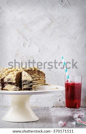 Sliced Homemade Birthday Honey Cake with chocolate cream, served on white ceramic plate over white wooden table with b-day candles and glass of red juice. With plastered. Retro filter effect - stock photo