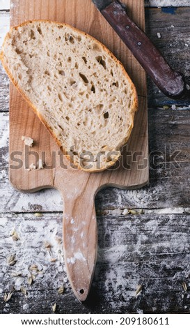 Sliced homemade bread on wooden cutting board with vintage knife, served over wooden table with flour. Top view - stock photo