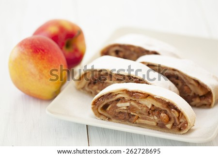 sliced into pieces apple strudel and fresh apples on wooden background - stock photo