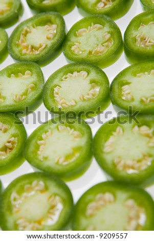 Sliced jalapeno pepper sections arranged on a white surface.