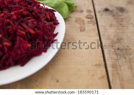 Sliced juicy radish and lettuce on a white plate. Shot on the left side of a wooden table. - stock photo