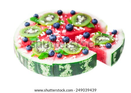Sliced juicy watermelon pizza isolated on white, closeup view from above. Ingredients are watermelon, blueberries, kiwi, mint, and coconut shavings. - stock photo