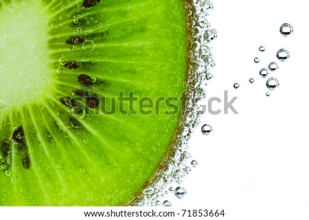 sliced kiwi covered with bubbles - stock photo