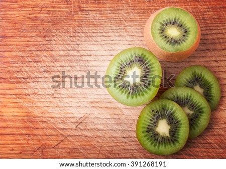 Sliced  Kiwi Fruits on the Textured Wooden Background with Free Space on the Right Side