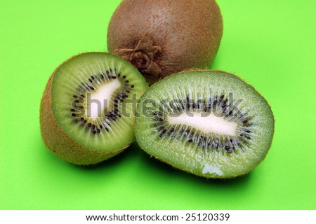 Sliced kiwi half with whole kiwi with green background
