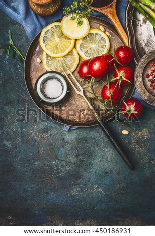 Sliced lemon and cooking ingredients on dark rustic background, top view, place for text - stock photo