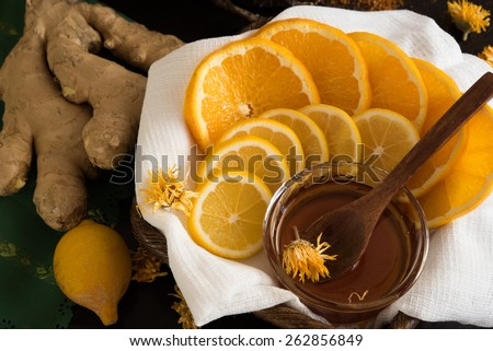 Sliced lemon and orange in basket with honey, ginger root and lemon behind - stock photo