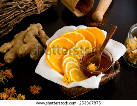 Sliced lemon and orange in busket with honey and ginger root behind - stock photo