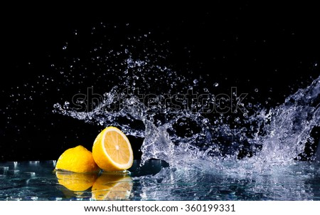Sliced lemon in the water on black background. Fresh lemons with water splash. Dynamics of a liquid, juicy appetizing lemon and glass with splashed out water on a dark surface of a table - stock photo