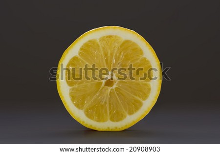 Sliced lemon isolated on a dark gray background - stock photo