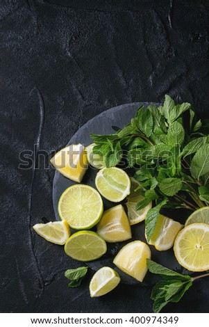 Sliced Lime and lemons with bunch of fresh mint on black slate stone board over black textured background. Top view. - stock photo