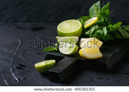 Sliced Lime and lemons with bunch of fresh mint on black wooden chopping board over black textured background - stock photo