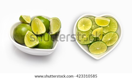 sliced lime  in a heart shaped bowl, isolated on white - stock photo