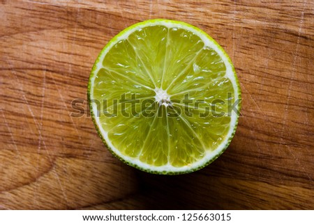 Sliced lime on a wooden chopping board - stock photo