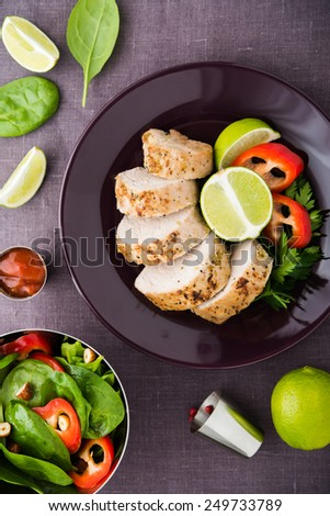 Sliced lime pork tenderloin and fresh healthy spinach salad on dark background top view. - stock photo