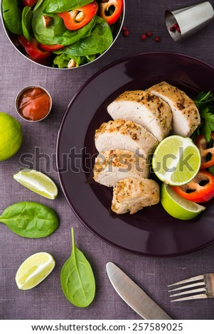Sliced lime pork tenderloin and fresh healthy spinach salad on dark background top view. Healthy food. - stock photo
