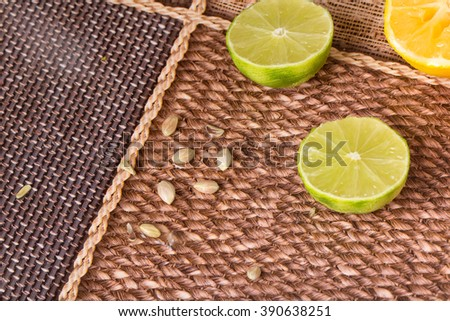 Sliced limes and seeds closeup on a table as a background. - stock photo