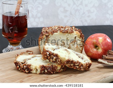 Sliced loaf of apple cinnamon pound cake with a pecan topping.  Selective focus on sliced pieces.