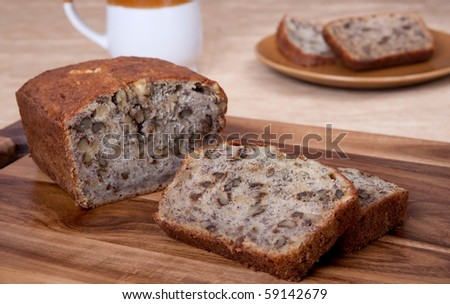 sliced loaf of banana walnut bread on a cutting board with one serving of two slices and a mug in the background - stock photo