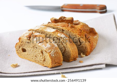 Sliced loaf of bread with crispy crust - stock photo