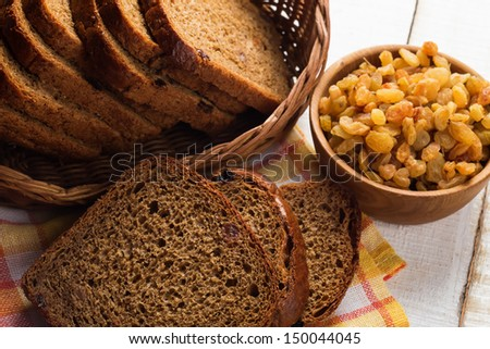 Sliced loaf of bread with raisins on wooden background. Selective focus. - stock photo