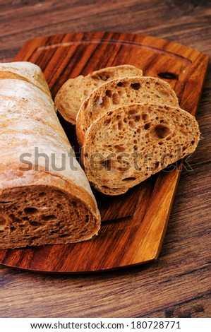 Sliced loaf of italian bread on a cutting board - stock photo