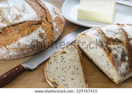 Sliced loaf of  Oatmeal and Flax Seed bread with butter - stock photo